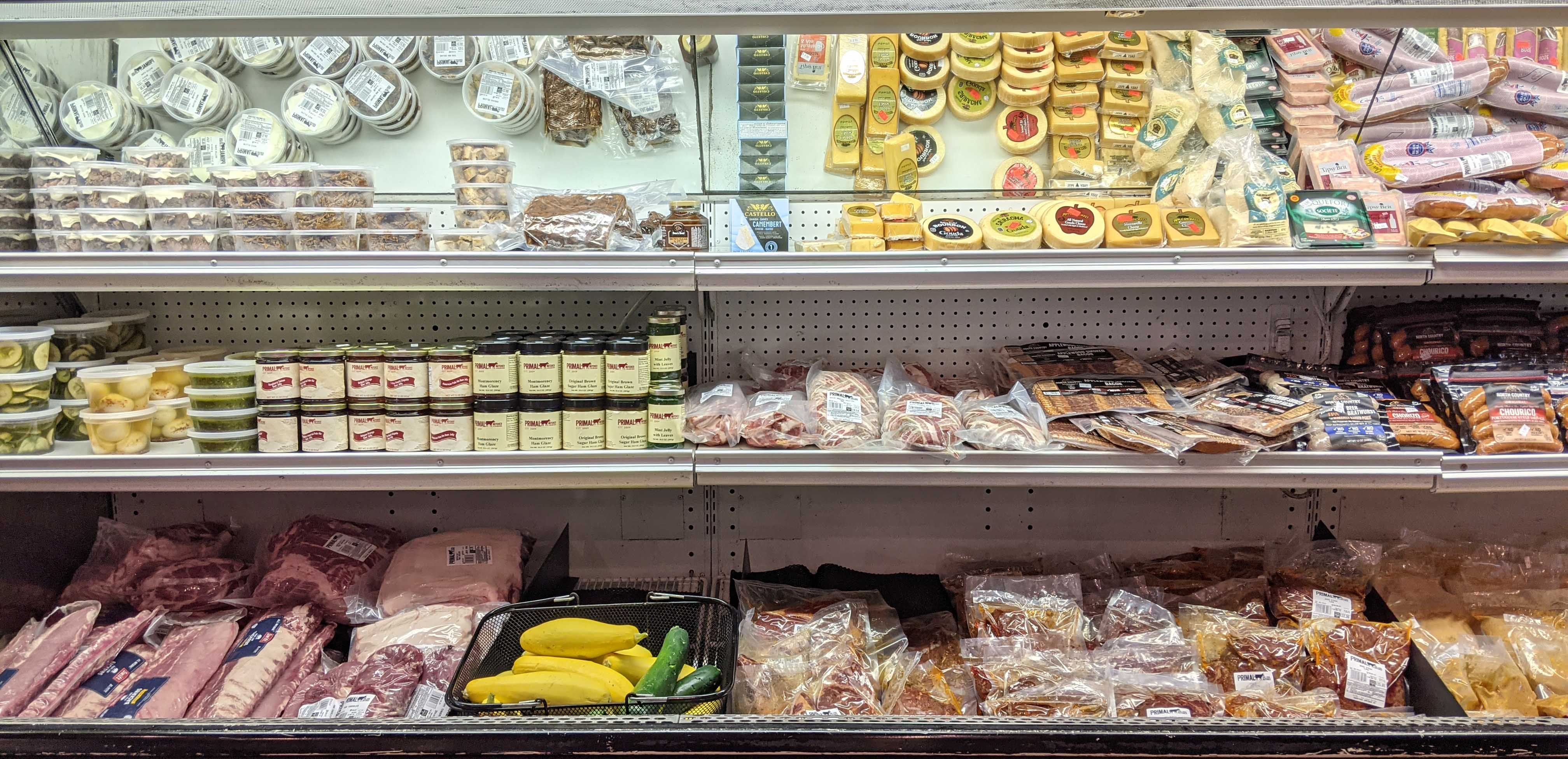 Fully stocked grocery case with fresh vegetables meat and condiments at Primal Butcher shop